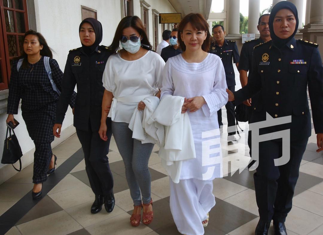 赖彩云(右)及蔡玲妹因涉嫌金字塔金钱游戏,周三被贸消部官员押往吉隆坡法庭面控。(摄影:骆曼)